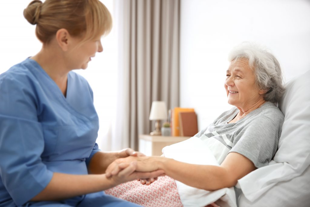 Caregiver massaging hand of senior woman at home